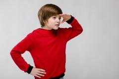 Pequeño muchacho caucásico curioso confiado lindo en el suéter rojo que busca algo en fondo gris Foto de archivo libre de regalías