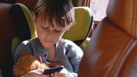 Pequeño muchacho caucásico de 4-6 años emocionado feliz que sonríe, usando el smartphone que se sienta en asiento de la seguridad metrajes