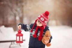 Pequeño muchacho caucásico lindo con el oso de peluche y la linterna roja, playi Fotos de archivo