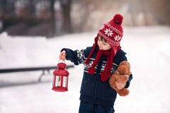 Pequeño muchacho caucásico lindo con el oso de peluche y la linterna roja, playi Foto de archivo