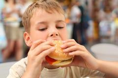 Pequeño muchacho caucásico que come la hamburguesa Imágenes de archivo libres de regalías