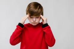 Pequeño muchacho caucásico triste confiado lindo en el suéter rojo que tiene dolor de cabeza en fondo gris Foto de archivo libre de regalías