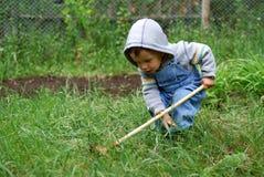 Pequeño muchacho con el rastrillo Imagen de archivo