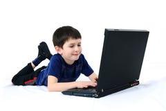 Pequeño muchacho con una computadora portátil Imágenes de archivo libres de regalías