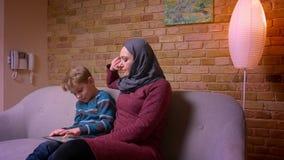 Pequeño muchacho concentrado que juega al juego en la tableta y su madre musulmán en hijab observando su actividad en casa almacen de video