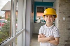 Pequeño muchacho de 6 años que presenta por una ventana con un casco amarillo Imágenes de archivo libres de regalías