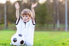 Pequeño muchacho de la fan en la visión pública del fútbol o del partido de fútbol Imágenes de archivo libres de regalías