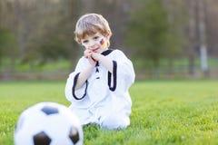 Pequeño muchacho de la fan en la visión pública del fútbol o del partido de fútbol Fotos de archivo libres de regalías