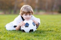 Pequeño muchacho de la fan en la visión pública del fútbol o del partido de fútbol Fotografía de archivo