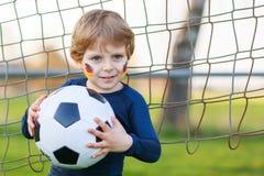 Pequeño muchacho de la fan en la visión pública del fútbol o del partido de fútbol Foto de archivo