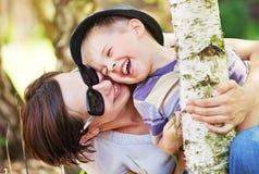 Pequeño muchacho de risa abrazado por su madre Imágenes de archivo libres de regalías