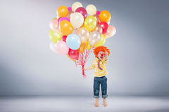 Pequeño muchacho de salto que sostiene el manojo de globos foto de archivo libre de regalías
