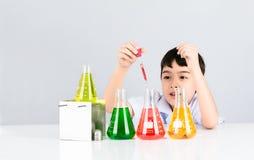 Pequeño muchacho del científico con el cubilete colorido en la tabla blanca Fotos de archivo