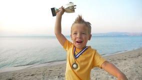 Pequeño muchacho del ganador con la medalla y la taza almacen de video