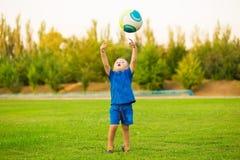 Pequeño muchacho divertido en fútbol del juego del estadio en verano fotografía de archivo