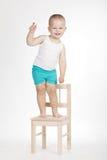 Pequeño muchacho divertido en silla imagen de archivo libre de regalías
