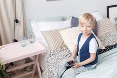 Pequeño muchacho elegante con el teléfono móvil, asientos en cama en dormitorio Concepto de la tecnología Foto de archivo libre de regalías