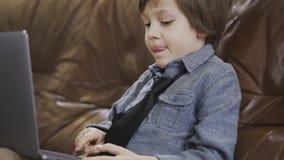 Pequeño muchacho emocionado que trabaja en un ordenador portátil en el sofá de cuero metrajes