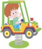 Pequeño muchacho en un oscilación del coche del juguete en un patio foto de archivo libre de regalías
