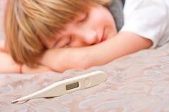 Pequeño muchacho enfermo que miente en cama con el termómetro digital Imágenes de archivo libres de regalías