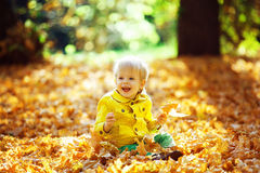 Pequeño muchacho feliz en la chaqueta amarilla que juega con las hojas Imagen de archivo
