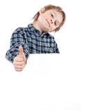 Pequeño muchacho feliz que lleva a cabo a una tarjeta en blanco contra pizca Imagenes de archivo