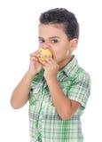 Pequeño muchacho hambriento que come la fruta Imagen de archivo libre de regalías
