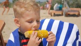 Pequeño muchacho hambriento que come maíz en la playa del mar Foco en el maíz hervido Primer metrajes