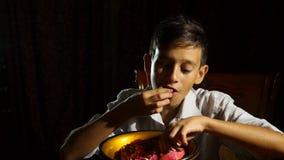 Pequeño muchacho hambriento un vegetariano que come una granada con avaricia en la noche 4k, a cámara lenta almacen de video