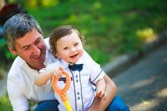Pequeño muchacho hermoso en los brazos de su padre Imagenes de archivo