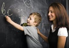 Pequeño muchacho lindo con el profesor en sala de clase Imagen de archivo libre de regalías
