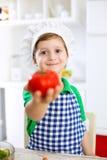 Pequeño muchacho lindo del niño con el sombrero del cocinero que sostiene el tomate Foto de archivo