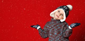 Pequeño muchacho lindo en un sombrero con el pompom y los guantes, los brazos extendidos al lado y los copos de nieve de las capt foto de archivo