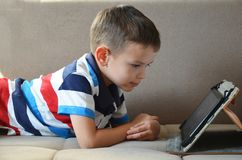 Pequeño muchacho lindo en una camiseta verde que juega a juegos en una tableta y que mira historietas Niño con la tableta fotos de archivo libres de regalías