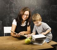 Pequeño muchacho lindo en vidrios con el profesor real joven, el estudiar de la sala de clase imagen de archivo