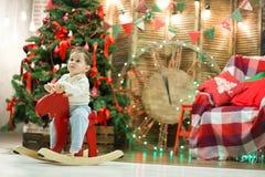 Pequeño muchacho lindo feliz que monta el caballo mecedora de madera delante del árbol de navidad y presentes en tiempo de la Nav Imágenes de archivo libres de regalías