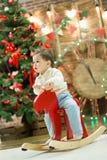 Pequeño muchacho lindo feliz que monta el caballo mecedora de madera delante del árbol de navidad y presentes en tiempo de la Nav Fotos de archivo libres de regalías