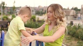 Pequeño muchacho lindo que besa a su mamá mientras que juega en el patio en el parque almacen de metraje de vídeo