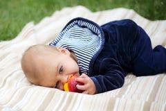 Pequeño muchacho lindo que come un melocotón en parque del verano Imagenes de archivo