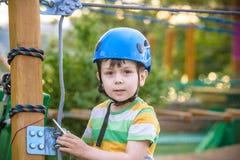 Pequeño muchacho lindo que disfruta de actividad en un parque de la aventura que sube en un día soleado del verano niño que sube  Fotos de archivo libres de regalías