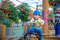 Pequeño muchacho lindo que disfruta de actividad en un parque de la aventura que sube en un día soleado del verano niño que sube  Fotos de archivo