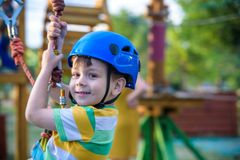 Pequeño muchacho lindo que disfruta de actividad en un parque de la aventura que sube en un día soleado del verano niño que sube  Foto de archivo libre de regalías