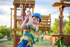 Pequeño muchacho lindo que disfruta de actividad en un parque de la aventura que sube en un día soleado del verano niño que sube  Fotografía de archivo