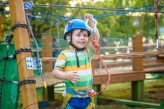 Pequeño muchacho lindo que disfruta de actividad en un parque o de la aventura que sube Imágenes de archivo libres de regalías