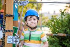 Pequeño muchacho lindo que disfruta de actividad en un parque o de la aventura que sube Imagen de archivo