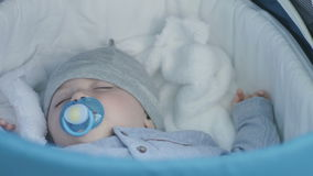 Pequeño muchacho lindo que duerme en el cochecito de niño almacen de metraje de vídeo