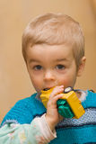 Pequeño muchacho lindo que muerde su juguete plactic del coche Imagen de archivo libre de regalías