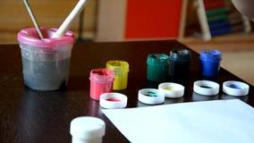 Pequeño muchacho lindo que pinta en casa la tarjeta en la tabla el muchacho dibuja pinturas y un cepillo Pensativo, serio El espe almacen de video