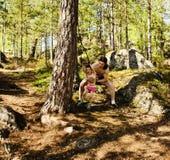 Pequeño muchacho lindo que salta con el amortiguador auxiliar en el bosque, entrenando con el papá Imágenes de archivo libres de regalías