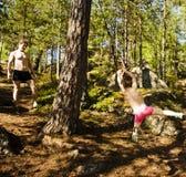 Pequeño muchacho lindo que salta con el amortiguador auxiliar en el bosque, entrenando con el papá Foto de archivo
